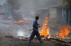 A policeman walks in front of a burning barricade during a protest against Burundi's President Pierre Nkurunziza and his bid for a third term in Bujumbura, Burundi, May 22, 2015. REUTERS/Goran Tomasevic